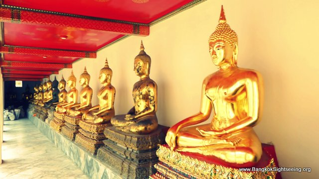 line of Buddha statues in subduing mara pose at Wat Po temple
